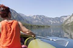 Woman paddle on calm mountain lake Royalty Free Stock Image