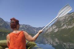 Woman paddle on calm mountain lake Stock Image