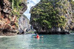 Woman paddles kayak in the tropical sea stock photography