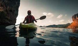 Woman paddles kayak. In the calm sea among the islands Stock Photos