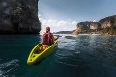 Woman paddles kayak. In a calm sea among the tropical islands Royalty Free Stock Image