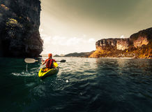 Woman paddles kayak. In the calm sea among the tropical islands Royalty Free Stock Images