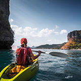 Woman paddles kayak. In the calm sea among the tropical islands Royalty Free Stock Photography
