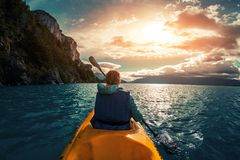 Woman paddles kayak royalty free stock image