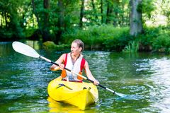 Woman paddling with canoe on forest river Stock Photos
