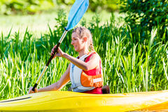 Woman paddling with canoe on river Stock Photo