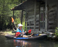 Woman Paddling by Floating Cabin - MorrisonSprings Royalty Free Stock Photography