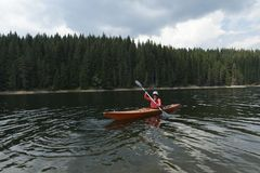 Woman paddling with her sit-in kayak Royalty Free Stock Images