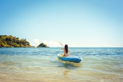 Woman paddling on a kayak on sea in clear water. Enjoying the summer stock photo