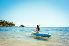 Woman paddling on a kayak on sea in clear water. Enjoying the summer stock image