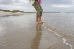 Woman paddling in sea, low section Stock Photos