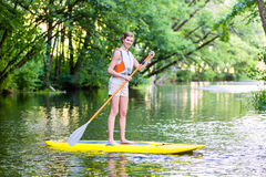 Woman paddling with surfboard sup on forest river. In summer stock photos