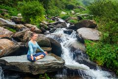 Woman in Padmasana outdoors Stock Photo