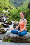 Woman in Padmasana outdoors royalty free stock image
