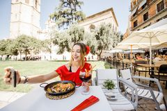 Woman with paella dish in Valencia. Young woman in red dress photographing sea Paella, traditional Valencian rice dish, sitting outdoors at the restaurant in royalty free stock photos