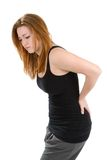 Woman Pain Back. Woman with a pain in her back bends over rubbing the spot to relieve the discomfort Stock Photo