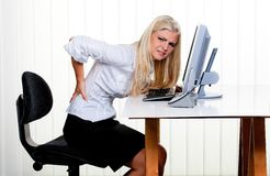 Woman with pain in the back office. Young woman with pain in the back office Stock Image
