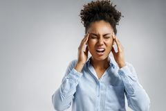 Woman with pain in her temples. Photo of african american woman in blue shirt suffering from stress or a headache grimacing in pain on gray background. Medical royalty free stock photos
