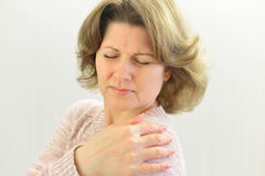 Woman with pain in his shoulder on  light background Royalty Free Stock Photo