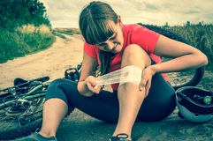 Woman with pain in knee after falling down from bicycle Stock Photos