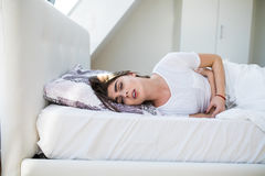 Woman in pain lying on bed Stock Image