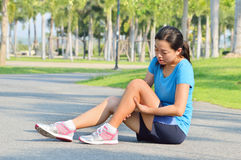 Woman in pain while running in park Stock Image