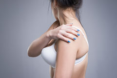 Woman with pain in shoulder, ache in the human body. On gray studio background stock photography