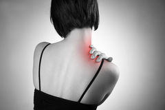 Woman with pain in shoulder. Pain in the human body. Black and white photo with red dot stock photos