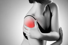 Woman with pain in shoulder. Pain in the human body. Black and white photo with red dot royalty free stock image