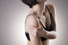 Woman with pain in shoulder. Pain in the human body. On gray background stock photos