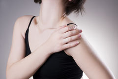 Woman with pain in shoulder. Pain in the human body. On a gray background stock photography