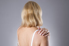 Woman with pain in shoulder. Pain in the human body. On a gray background royalty free stock image