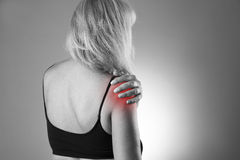 Woman with pain in shoulder. Pain in the human body on a gray background. Black and white photo with red dot stock image
