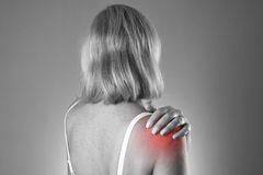 Woman with pain in shoulder. Pain in the human body. On a gray background. Black and white photo with red dot stock image