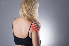Woman with pain in shoulder. Pain in the human body on a gray background. With red dot stock photo