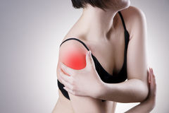 Woman with pain in shoulder. Pain in the human body. On a gray background with red dot stock photos