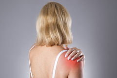 Woman with pain in shoulder. Pain in the human body. On a gray background with red dot royalty free stock photos
