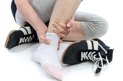 Woman with painful ankle. Woman holding her sore ankle Stock Photography