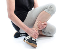 Woman with painful ankle. A woman holding her sore ankle Stock Image