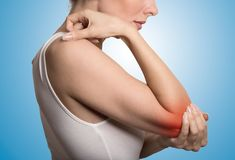 Woman with painful elbow on blue background Royalty Free Stock Image