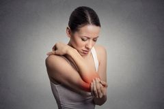 Woman with painful elbow on gray background Stock Photos