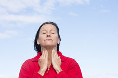 Woman with painful throat ache. Portrait attractive mature woman stressed and suffering from painful throat ache, closed eyes, concentrated, with hands on throat Stock Photos