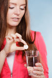 Woman with painkiller pill and water. Health care. Stock Photography
