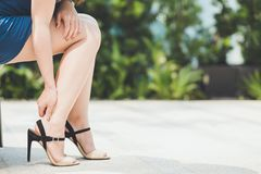 Woman pains ankle from wearing high heel shoes. Health and medical concept Royalty Free Stock Photo