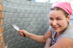 Woman with paint brush in hands painting a brick wall. Woman with paint brush in the hands painting a brick wall Royalty Free Stock Images