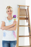 Woman with paint brush looking away in new house. Beautiful young woman with paint brush looking away in the new house Stock Photos