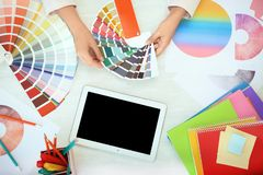Woman with paint color palette samples and tablet. At table, top view royalty free stock photography