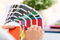 Woman with paint color palette samples. On blurred background, closeup royalty free stock image