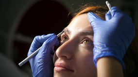 Woman paint her eyebrow. A young red-haired woman paint her eyebrow with a dark master paint to achieve the perfect shape in medical gloves of blue Stock Photos