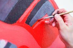 Woman paint little car stock photo